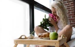 Den härliga kvinnan tycker om blommor på frukosten Arkivfoto