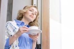 Den härliga kvinnan tycker om kaffe och tänker royaltyfria foton
