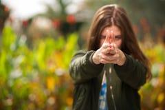 Den härliga kvinnan vek hennes armar i form av pistolen arkivfoto