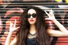 Den härliga kvinnaståenden vaggar in stil på stads- bakgrund Arkivbild