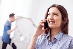 Den härliga kvinnliga arbetaren använder en telefon Royaltyfria Bilder