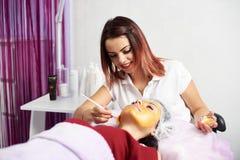 Den härliga kvinnliga cosmetologisten ler, medan applicera den guld- maskeringen till en framsida av en brunettklient i en skönhe arkivfoto
