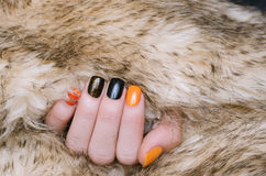 Den härliga kvinnliga handen med apelsinen och svart spikar konst fotografering för bildbyråer