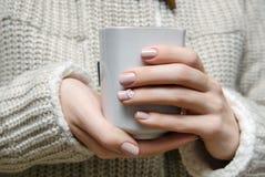 Den härliga kvinnliga handen med beiga spikar design royaltyfria bilder
