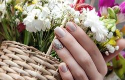 Den härliga kvinnliga handen med beiga spikar design royaltyfri fotografi