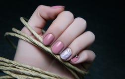 Den härliga kvinnliga handen med beiga spikar design arkivfoto