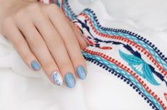 Den härliga kvinnliga handen med blått spikar design fotografering för bildbyråer