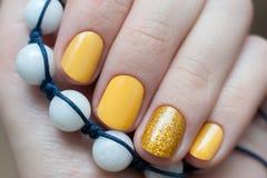Den härliga kvinnliga handen med guling spikar design arkivbild