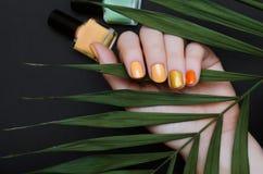 Den härliga kvinnliga handen med guling spikar design med blänker arkivfoto