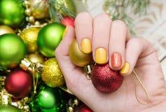 Den härliga kvinnliga handen med guling spikar design Julmanikyr arkivfoton