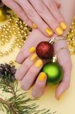 Den härliga kvinnliga handen med guling spikar design Julmanikyr royaltyfria foton