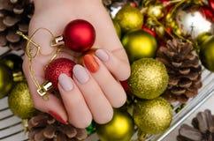 Den härliga kvinnliga handen med jul spikar design royaltyfri bild
