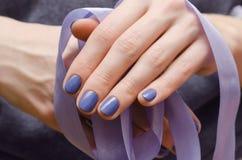 Den härliga kvinnliga handen med lilor spikar design fotografering för bildbyråer