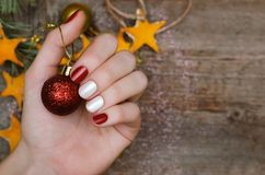 Den härliga kvinnliga handen med rött och vitt spikar design Julmanikyr Arkivbilder