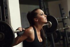 Den härliga kvinnliga idrottsman nen squats med skivstången royaltyfri foto