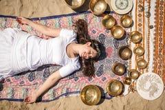 Den härliga kvinnliga massagen för hälerienergiljudet med att sjunga bowlar på en flodbank arkivbild