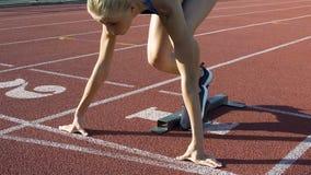 Den härliga kvinnliga spårlöparen lämnar startgrop i ultrarapid, konkurrens arkivfilmer