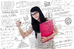Den härliga kvinnliga studenten skriver på genomskinligt vitt bräde arkivbilder