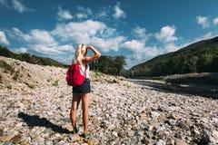 Den härliga kvinnliga turisten står på flodbanken och tycker om sikt av berg i sommar arkivfoton