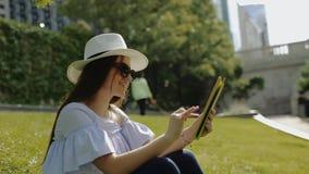 Den härliga kvinnlign arbetar med minnestavlaPC:n som sitter på gräs parkerar in stock video