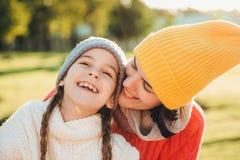 Den härliga kvinnlign i guling stucken hatt kysser hennes förtjusande lilla barn, har underbar oförglömlig tid tillsammans Småbar royaltyfri bild