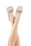Den härliga kvinnlign lägger benen på ryggen i ljusa skor med bergkristaller Spensliga ben, höga häl, ljusa mousserande kristalle Royaltyfri Foto
