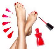 Den härliga kvinnlign lägger benen på ryggen med röd pedikyr och spikar polermedel Fotografering för Bildbyråer