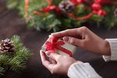 Den härliga kvinnlign räcker att rymma en julklapp i ask med den röda pilbågen arkivbild