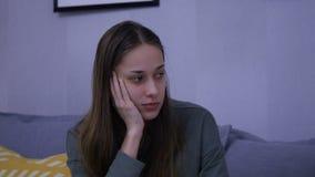 Den härliga långa Haired kvinnan sitter på Grey Cosy Sofa lager videofilmer