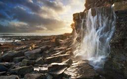 Den härliga landskapbildvattenfallet som flödar in i, vaggar på stranden