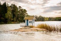 Den härliga landskapsikten av ett litet bad förlägga i barack stugan på en vagga i en sjö som omgavs av träd och vassen royaltyfria bilder