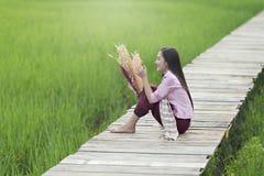 Den härliga laotiska kvinnan som bara sitter med, dekorerar blomman på träbron i grön risfält arkivfoton