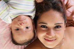 Den härliga latinamerikanska lyckliga modern med behandla som ett barn att ligga ner Arkivfoto