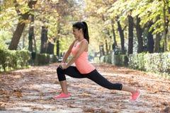 Den härliga latinamerikanska sportkvinnan i sportswearen som sträcker kroppen som ler därefter lycklig görande böjlighet, övar arkivfoton