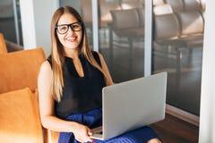 Den härliga le affärskvinnan använder en bärbar dator fotografering för bildbyråer
