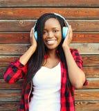 Den härliga le afrikanska kvinnan med hörlurar lyssnar till musik royaltyfria bilder