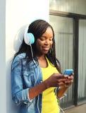 Den härliga le afrikanska kvinnan med hörlurar lyssnar till musik och användasmartphonen Arkivfoton