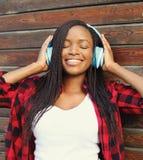 Den härliga le afrikanska kvinnan med hörlurar som tycker om, lyssnar musik i stad royaltyfri bild