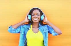 Den härliga le afrikanska kvinnan med hörlurar som tycker om, lyssnar till musik Arkivbild