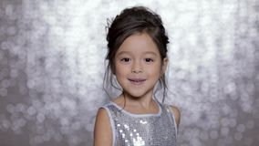 Den härliga le flickan för det lilla barnet i försilvrar klänningdans på bakgrund av försilvrar bokeh arkivfilmer