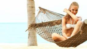 Den härliga le kvinnan med det långa sammanträdekorset för blont hår lade benen på ryggen i en hängmatta stock video