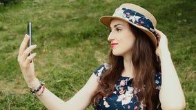 Den härliga le kvinnan med röda sinnliga kanter tar Selfie genom att använda hennes mobiltelefon stock video