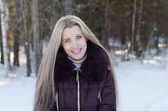 Den härliga le kvinnan på vinter går Royaltyfri Foto