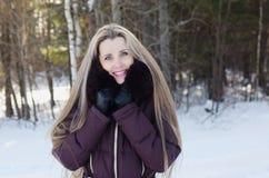 Den härliga le kvinnan på vinter går Arkivfoto