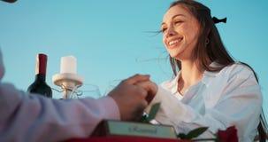 Den härliga le kvinnan talar med hennes vän- och innehavhänder under den utomhus- romantiska matställen längd i fot räknat 4k stock video