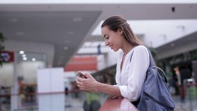Den härliga le kvinnan tar en inkommande appell till en mobiltelefon inom gallerian stock video