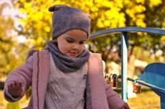 Den härliga le lilla flickan i höst parkerar fotografering för bildbyråer