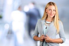 Den härliga le ståenden för affärskvinna Blå bakgrund bakom Royaltyfri Bild