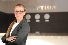 Den härliga le ståenden för affärskvinna Le den kvinnliga receptionisten Arkivfoto