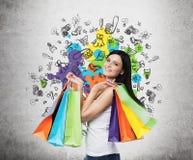 Den härliga le unga kvinnan med de färgglade shoppingpåsarna från infallet shoppar Royaltyfri Bild